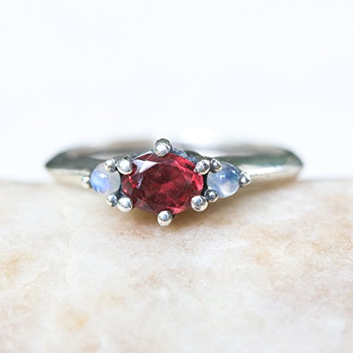 - Oval faceted Garnet ring and cabochon tiny moonstone side set gems in prongs setting with sterling silver band