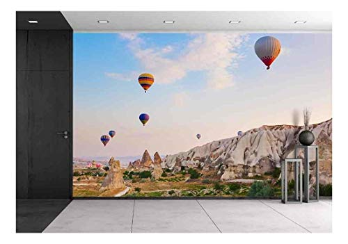wall26 - Hot Air Balloon Flying Over Rock Landscape at Cappadocia Turkey - Removable Wall Mural | Self-Adhesive Large Wallpaper - 66x96 inches