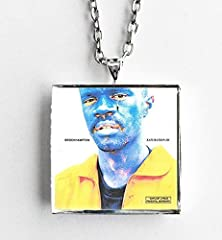 """This is a necklace featuring album art of the """"Saturation III"""" record by BROCKHAMPTON in a silvertone metal setting. The album cover pendant is 1"""" and on a 20"""" long silvertone neck chain. The necklace is individually handcrafted by me in the ..."""