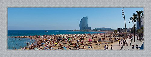 Tourists on the beach with W Barcelona hotel in the background, Barceloneta Beach, Barcelona, Catalonia, Spain by Panoramic Images Framed Art Print Wall Picture, Flat Silver Frame, 41 x 16 inches by Great Art Now