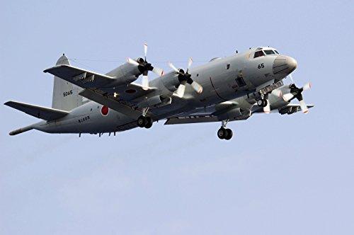 A Japan Maritime Self-Defense Force (JMSDF) P-3C Orion flies above the aircraft carrier USS Kitty Ha