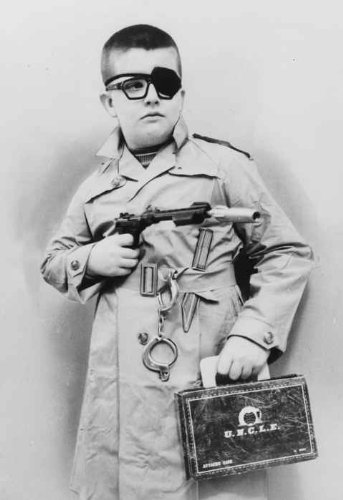 1966 TITLE: Alex Mumford Jr., 10 disguised as the man from uncle complete with eye patch, handcuffs, trench coat, knife, gun, briefcase, in Macy's Toy Dept. Vintage 8x10 Photograph - - Site Macy's