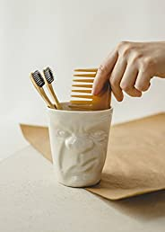 Modern white porcelain cup with a funny grumpy face for tea and cofee or toothbrushes pencils and makeup brush