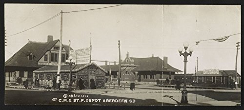 1911 Photo C. M. & St. P. depot, Aberdeen, S.D. Postcard shows depot of the Chicago, Milwaukee and Saint Paul Railroad in Aberdeen, South Dakota with an exhibit building touting