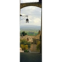 Umbrian countryside viewed through an alleyway Assisi Perugia Province Umbria Italy Poster Print (36 x 13)