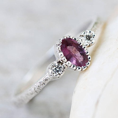 (Oval faceted purple sapphire ring in texture sterling silver band and twin side set diamond gemstones)