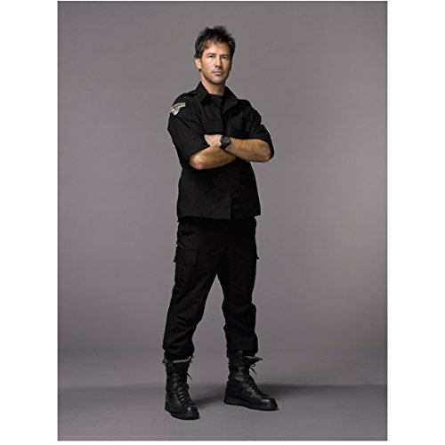 Joe Flanigan 8x10 Inch Photo Stargate Atlantis 6 Bullets The Other Sister Wearing All Black Gun Strapped to Leg Grey Background Pose 8 kn