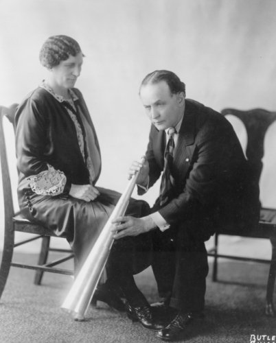 1926 photo Houdini and Mrs. Benninghofen, Chicago . Mrs. Benninghofen was a reformed spirit medium who had used a trumpet in her work. In these photographs she is seen demonstrating techniques of psychic deception to Houdini. The skill of spirit mediums was fully appreciated by Houdini who included the following statement in