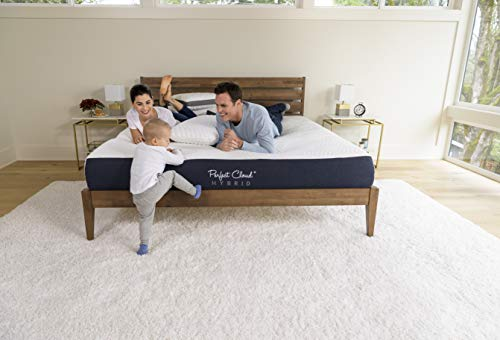 a happy couple lying on the Perfect Cloud Mattress while a smiling toddler tries to climb it playfully