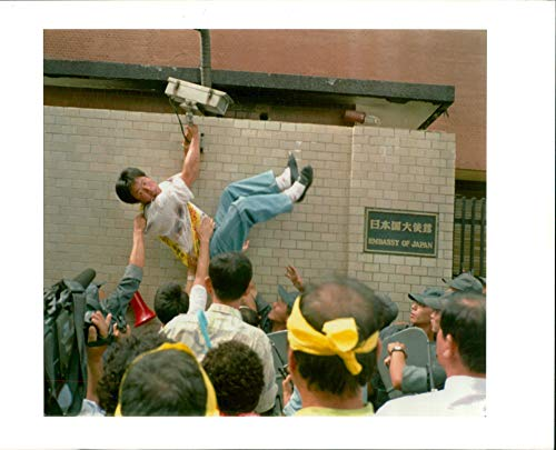 Vintage photo of south korea demonstration:riot police hold a protestor trying to scale over the wall.