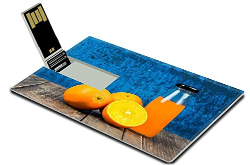 Luxlady 32GB USB Flash Drive 2.0 Memory Stick Credit Card Size Fresh orange and juice on vintage wooden table background IMAGE 39303687