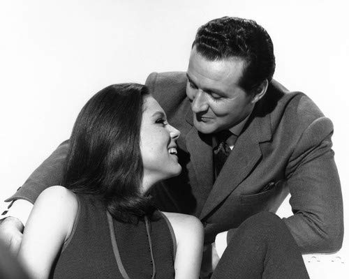 Patrick Macnee and Diana Rigg in The Avengers looking at each other smiling 8x10 Promotional Photograph