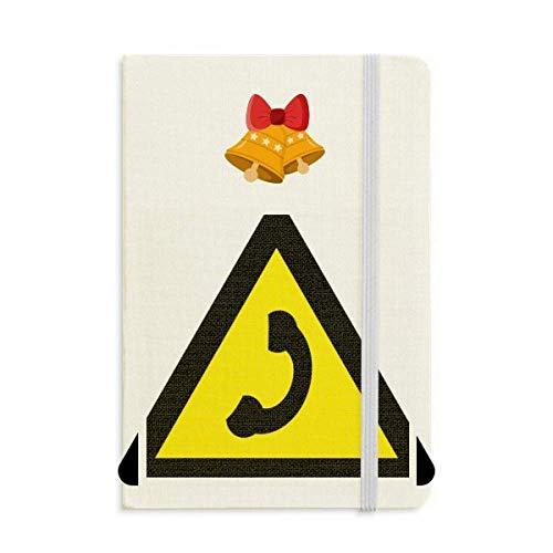 Cuaderno de notas con símbolo de advertencia amarillo y negro con cascabel navideño