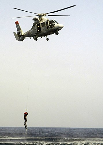 A Search and rescue swimmers (SAR) is raised out of the water by a Moroccan HH-65A Dolphin (Hh 65a Dolphin)