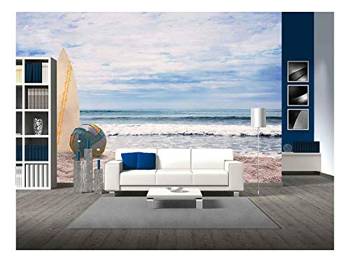 wall26 - Surfboard and Ball on Empty Beach Against Blue Sky and Turquoise Ocean. Summer. - Removable Wall Mural | Self-Adhesive Large Wallpaper - 100x144 inches