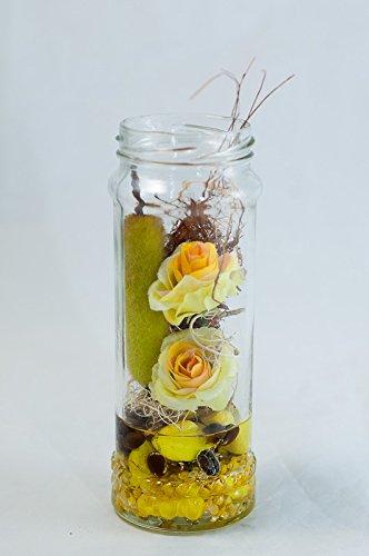 Centro de mesa con pequeñas rosas amarillas y pistón de caña en un ...