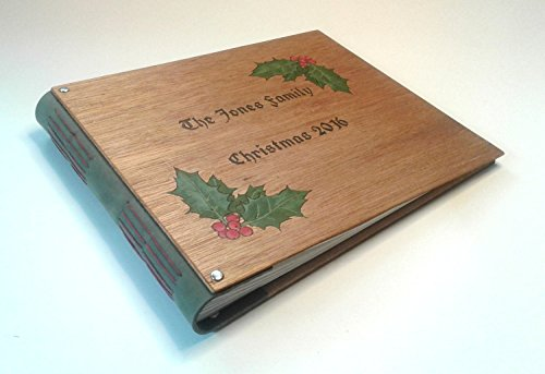 Personalized family Christmas photo album, hand-bound in wood and leather, with family name and holly decoration engraved on the cover. A package of photo corners for mounting photos is included. by Jonathan Day Book Art
