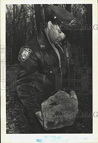 1991 Press Photo A police officer with a rock found under a girl's head