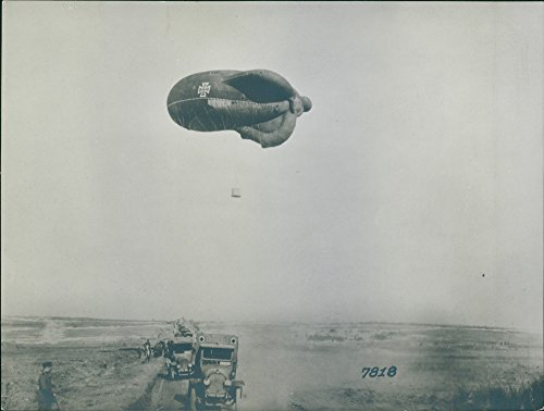 - Vintage photo of A hot air balloon flies over a marching military vehicles crossing a dirt road land,1914.