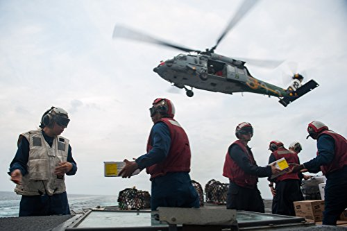 Sailors transfer food and supplies during a vertical replenishment aboard the guided-missile cruiser