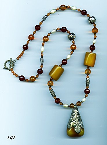 #141 Tibetan amber pendant encased in etched silver on a beaded necklace.