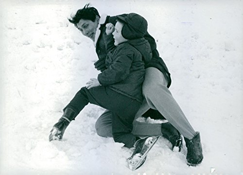 Old-fogeyish photo of American actor and singer Jack Palance is passing a joyful time with his little daughter Holly Palance, while they are playing on the ice