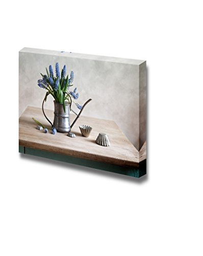 Still Life with Grape Hyacinths Arranged in an Antique Watering Can with Old Moulds on a Rustic Wooden Kitchen Table Wall Decor Wood Framed