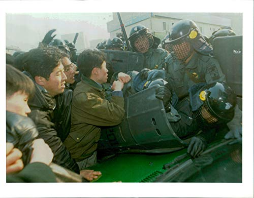 Vintage photo of south korea demonstration:a radical students grab a riot police officer.