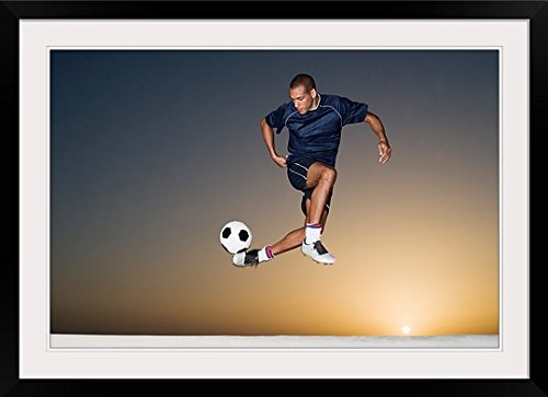 GreatBIGCanvas ''Soccer player kicking ball in mid air'' Photographic Print with Black Frame, 36'' x 24'' by greatBIGcanvas
