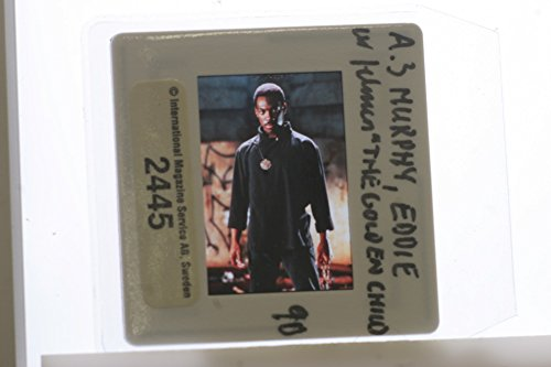 Slides photo of American comedian and actor Eddie Murphy being photographed dressed a black costume in a scene of 198639;s fantasy comedy film