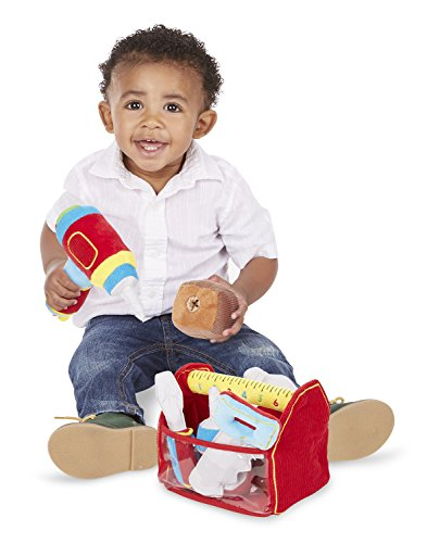 Child stages of play: Young baby boy playing with a power tool toy playset
