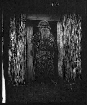 Photo: Ainu man holding staff,doorway,hut,villages,entrances,thatched,A - Foto Hut