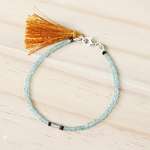 - Aquamarine beads bracelet and silver oxidized sticks at the center with gold color tassel on sterling silver lobster clasp closer