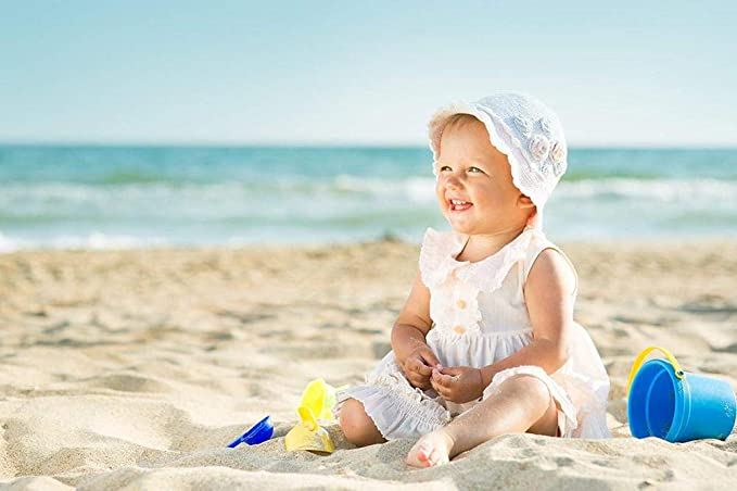 Malo dete devojčica sa kapicom u pesku na plaži