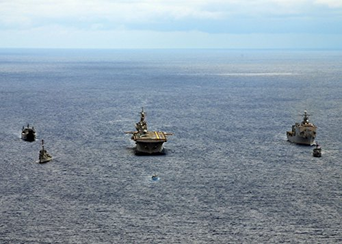 The forward-deployed amphibious assault ship USS Essex (LHD 2), center, steams in formation with, f
