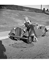Marilyn Monroe leaning against singer automobile
