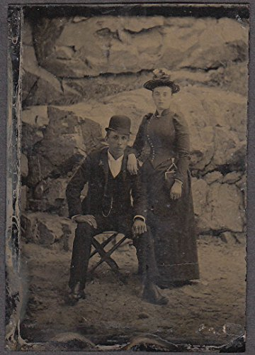 Seated man derby, standing woman straw hat tintype rock background 1860s