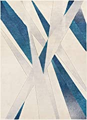 Sortie brings an ultra modern, geometric perspective to your home. A frantic pattern of lines and triangles is woven in sharp colors of dark and light blue on a background of grey and ivory. The abstract geometric pattern and bright colors ar...