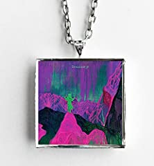 """This is a necklace featuring album art of the """"Give a Glimpse of What Yer Not"""" record by Dinosaur Jr. sealed in a silvertone metal setting. The album cover pendant is 1"""" and on a 20"""" long silvertone neck chain. The necklace is individually ha..."""
