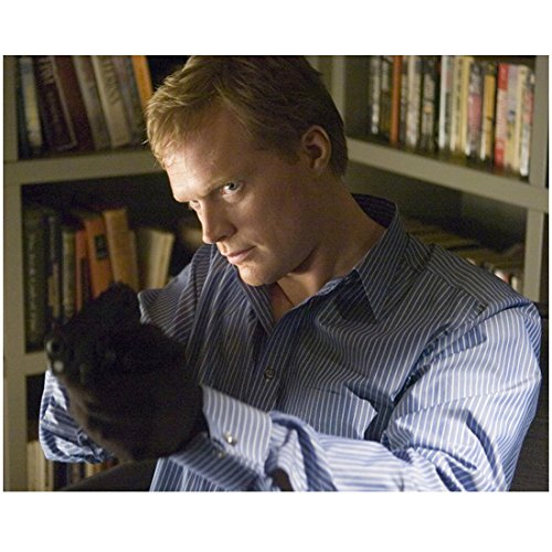 Paul Bettany standing in front of a bookshelf pointing forwards looking focused