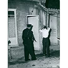 Vintage photo of A view of a police officer capturing a civilian on the street of Algeria.