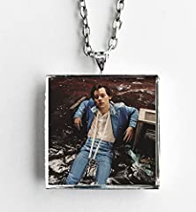 """This is a necklace featuring album art of the Self Titled import version record by Harry Styles sealed in a silvertone metal setting. The album cover pendant is 1"""" and on a 20"""" long silvertone neck chain. The necklace is individually handcraf..."""