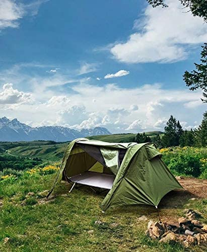 The Night Cat tent cot set up in a beautiful field with a mountain backdrop