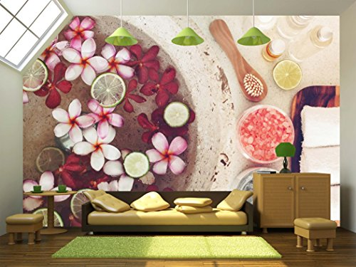 Foot bath in bowl with lime and tropical flowers spa pedicure treatment top view