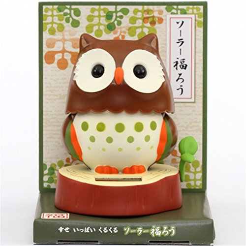 (dark brown owl solar powered bobble toy from Japan, uses light to power bobble head motion, with red brown tree stump base, with solar panel, turns head from side to side, with small green circles, wi)