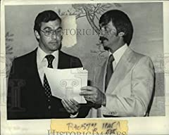 This is an original press photo. Dick Sakala (left) and hockey coach Charles Morison review papers Photo measures 9 x 7.25 inches. Photo is dated --1978.