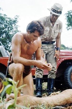 Ron Ely Tarzán Barechested arrodillado por Lion con Jeep en ...