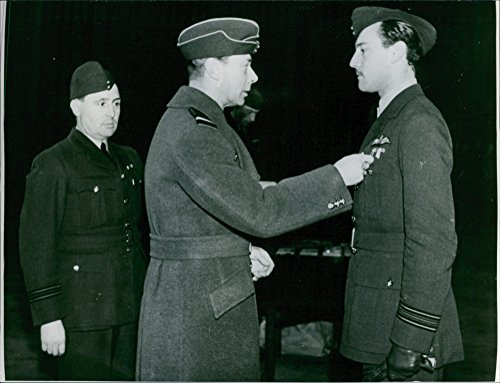 Vintage photo of King George VI standing and putting a merit medal of valor to a military officer.