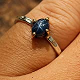 Oval-cabochon-blue-star-sapphire-ring-in-sterling-silver-bezel-and-brass-prong-setting-with-silver-hammer-texture-band