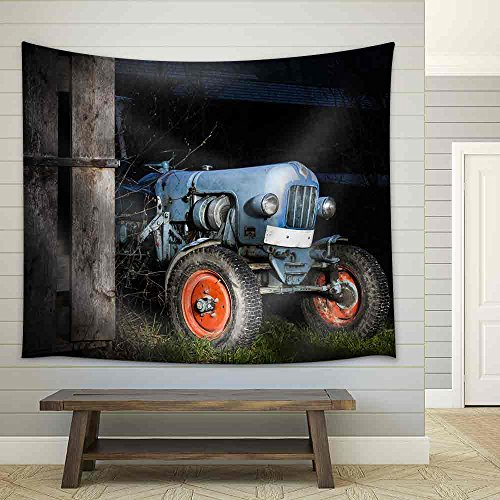 Blue Oldtimer Farming Tractor Standing Next to a Wooden Hut at Night with Red Painted Tires Fabric Wall Tapestry